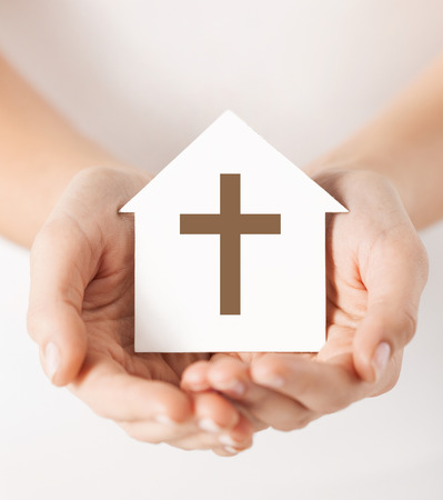 religion, christianity and charity concept - female hands holding paper house with christian cross symbol photo
