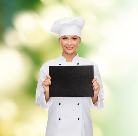 cooking, advertisement and food concept - smiling female chef, cook or baker with blank black paper photo