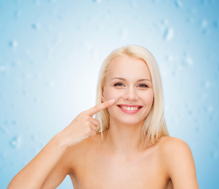 touching face: health and beauty concept - smiling young woman pointing to her nose