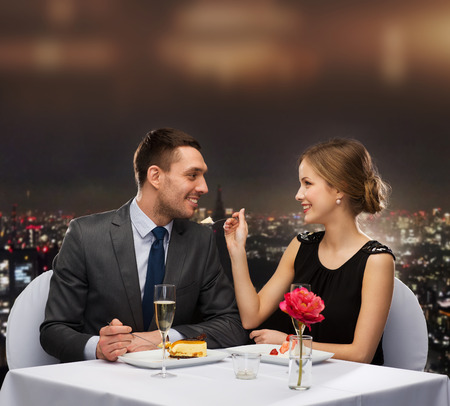 romantic evening with wine: restaurant, couple and holiday concept - smiling couple eating dessert at restaurant Stock Photo