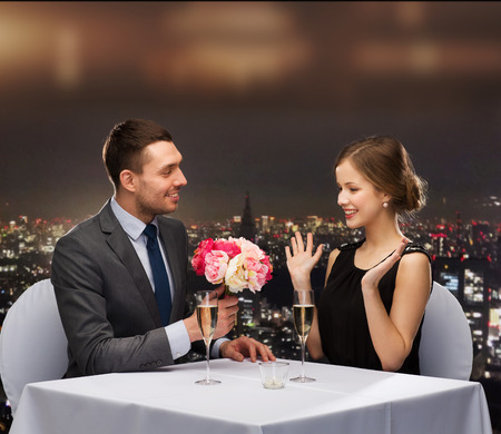 restaurant, couple and holiday concept - smiling man giving flower bouquet to woman at restaurant photo