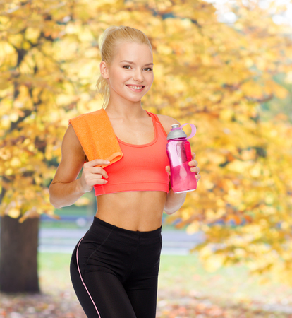 sport, exercise and healthcare concept - sporty woman with orange towel and water bottle photo