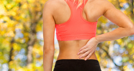 fitness, healthcare and medicine concept - close up of sporty woman touching her back photo