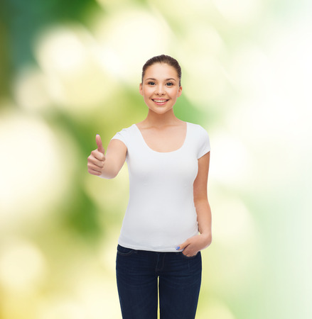 approvement: advertising, ecology, gesture and people concept - smiling young woman in blank white t-shirt showing thumbs up over green background