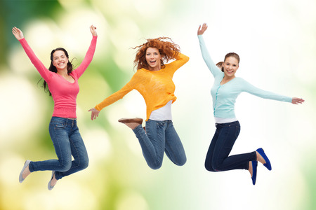 happiness, freedom, ecology, friendship and people concept - group of smiling young women jumping in air over green background photo