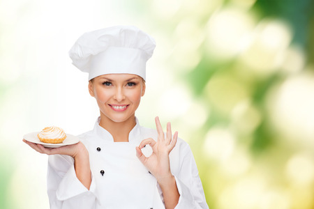 cooking and food concept - smiling female chef, cook or baker with pie on plate and ok sign photo