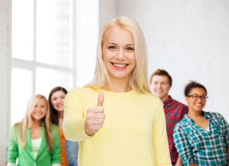happiness, gesture and people concept - smiling young woman in casual clothes showing thumbs up photo