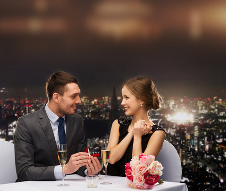 restaurant, couple and holiday concept - smiling man proposing to his girlfriend at restaurant Stockfoto