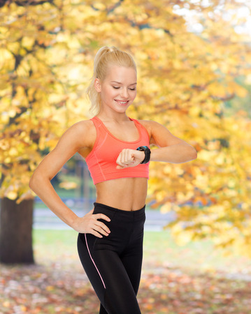 fitness, technology and exercising concept - smiling woman looking at heart rate monitor on hand photo