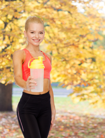 sport, fitness and diet concept - smiling sporty woman with protein shake bottle photo