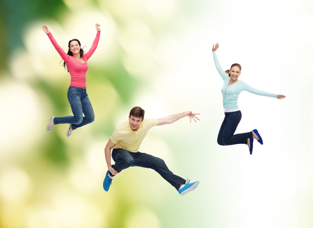 happiness, freedom, ecology, friendship and people concept - group of smiling teenagers jumping in air over green background photo