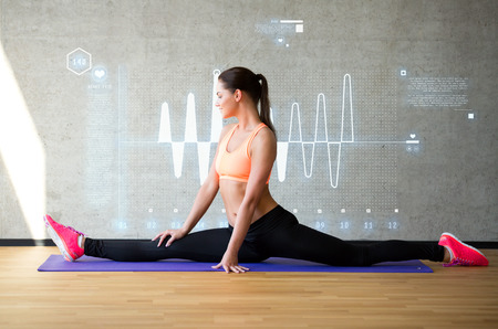 fitness, sport, training, future technology and lifestyle concept - smiling woman stretching leg on mat in gym over cardiogram projection photo