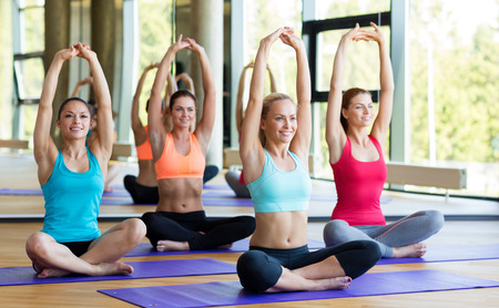 shaping: fitness, sport, training and lifestyle concept - group of smiling women stretching in gym