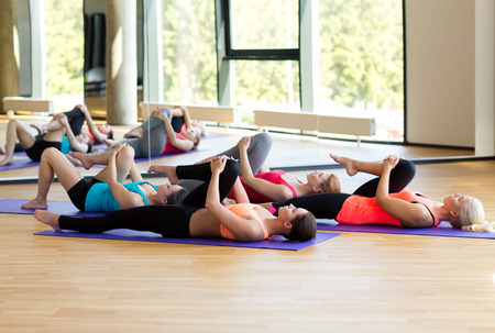 gym class: fitness, sport, training and lifestyle concept - group of women stretching in gym Stock Photo
