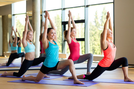 yoga: fitness, sport, training and lifestyle concept - group of smiling women stretching in gym