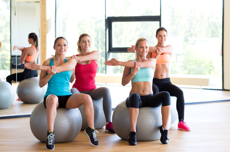 fitness, sport, training and lifestyle concept - group of smiling women with exercise balls in gym photo