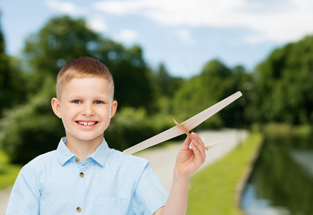 dreams, future, hobby, nature and childhood concept - smiling little boy holding wooden airplane model in his hand over park background photo