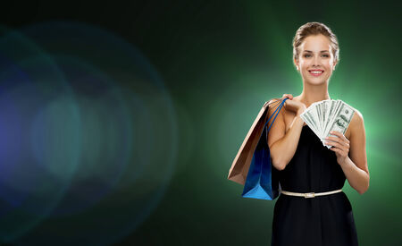 holiday spending: shopping, sale, gifts, money and holidays concept - smiling woman in dress with shopping bags and money over black background