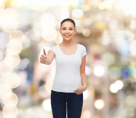 approvement: advertising, holidays, gesture and people concept - smiling young woman in blank white t-shirt showing thumbs up over sparkling background