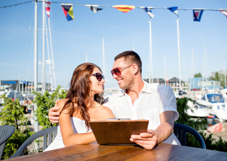 love, dating, people and food concept - smiling couple wearing sunglasses holding menu and looking to each other at cafe photo
