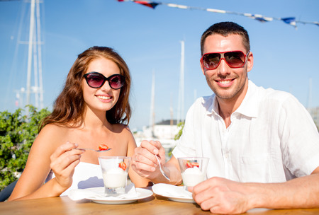 love, dating, people and food concept - smiling couple wearing sunglasses eating dessert at cafe photo