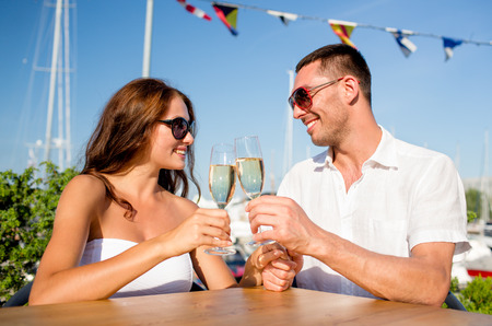 love, dating, people and holidays concept - smiling couple wearing sunglasses drinking champagne and looking to each other at cafe photo