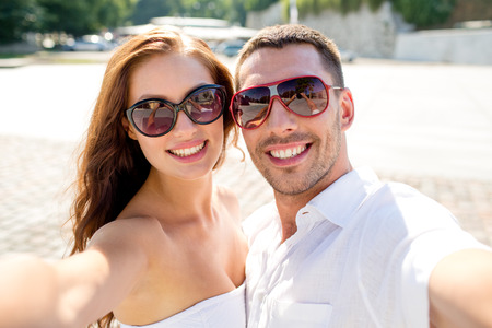 love, wedding, summer, dating and people concept - smiling couple wearing sunglasses making selfie in city photo