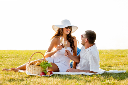 love, dating, people and holidays concept - smiling couple drinking champagne on picnic photo