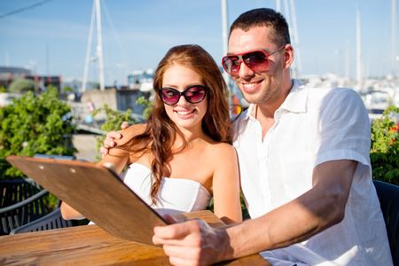 love, dating, people and food concept - smiling couple wearing sunglasses looking at menu on cafe terrace photo