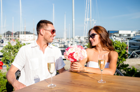 love, dating, happiness and people concept - smiling couple wearing sunglasses with bunch of flowers and champagne glasses looking to each other at cafe photo