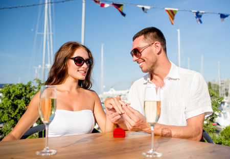 love, dating, people and holidays concept - smiling couple wearing sunglasses with champagne and small red gift box putting wedding ring on finger at cafe photo
