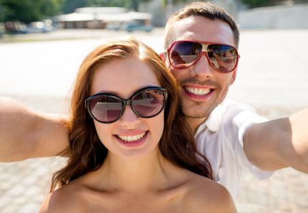 Liebe, Hochzeit, Sommer, Dating und Personen-Konzept - lächelnde Paar mit Sonnenbrille macht Selfie in Stadt