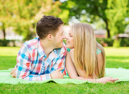 teenage love: holidays, vacation, love and friendship concept - smiling couple lying on blanket and touching noses in park Stock Photo