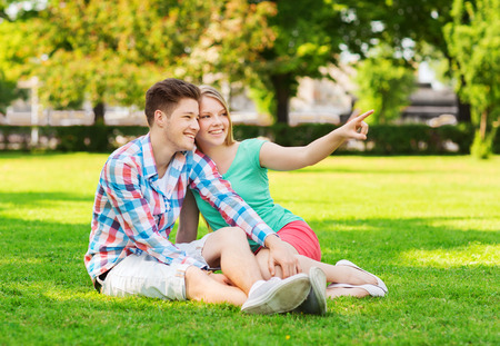 holidays, vacation, love and friendship concept - smiling couple sitting on grass and pointing finger in park photo