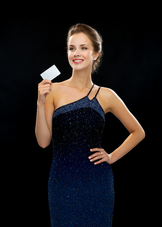 wealth, money, luxury and people concept - smiling woman in evening dress holding credit card over black background photo