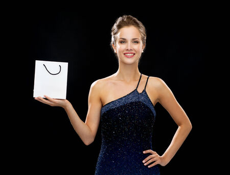 holydays: shopping, luxury, advertisement, holydays and sale concept - smiling woman with white blank shopping bag over black background Stock Photo