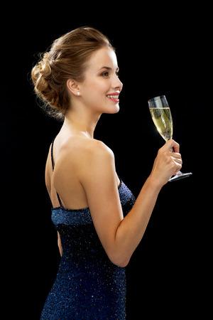 パーティー、ドリンク、休日、豪華さとお祝いのコンセプト - 黒の背景上のスパーク リング ワインのグラスとイブニング ドレスの女性の笑顔