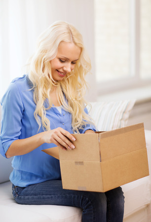 package: transportation, delivery, home and people concept - smiling woman opening cardboard box at home