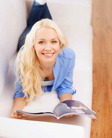 home, reading and leisure concept - smiling woman lying on couch and reading magazine at home