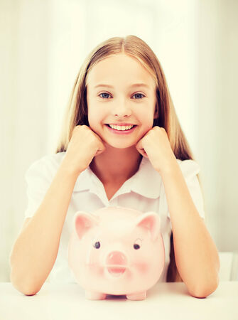 thrifty: education, school and money saving concept - child with piggy bank