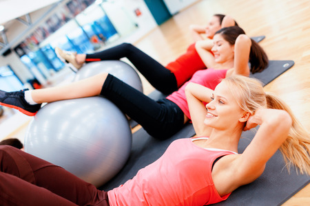 fitness woman: fitness, sport, training, gym and lifestyle concept - group of smiling people working out in pilates class Stock Photo