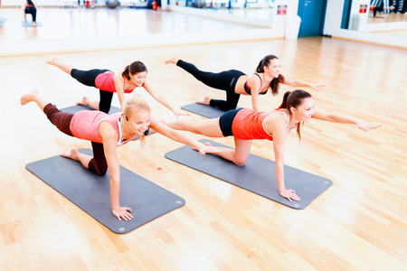 fitness, sport, training, gym and lifestyle concept - group of smiling women stretching on mats in the gym photo