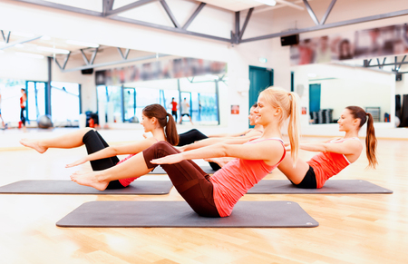 fitness trainer: fitness, sport, training, gym and lifestyle concept - group of smiling women exercising on mats in the gym