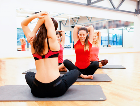 gym class: fitness, sport, training, gym and lifestyle concept - group of smiling women stretching on mats in the gym