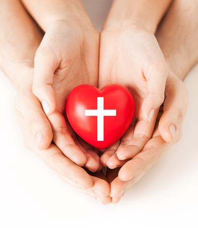 familia en la iglesia: religi�n, cristianismo y el concepto de la caridad - par de manos de la familia con el coraz�n rojo con el s�mbolo de la cruz cristiana Foto de archivo