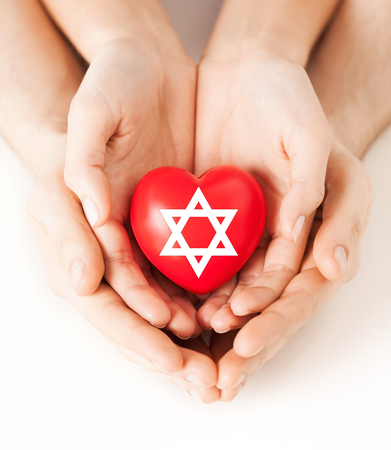 religion, christianity and charity concept - family couple hands holding red heart with star of david symbol Stock Photo