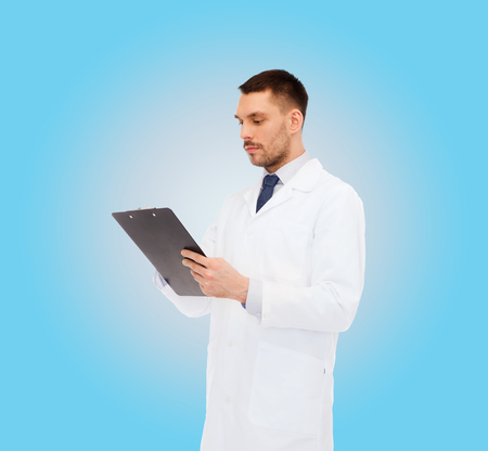 prescribing: medicine, profession, and healthcare concept - serious male doctor with clipboard writing prescription over white background