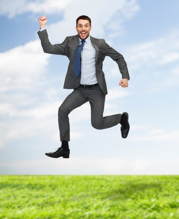 jump suit: business, education and people concept - smiling happy businessman jumping