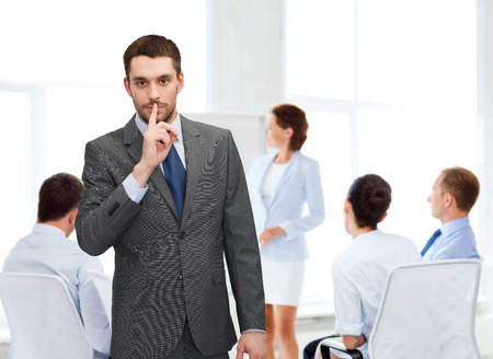 business, office, gesture and people concept - group of businessmen making hush sign in office
