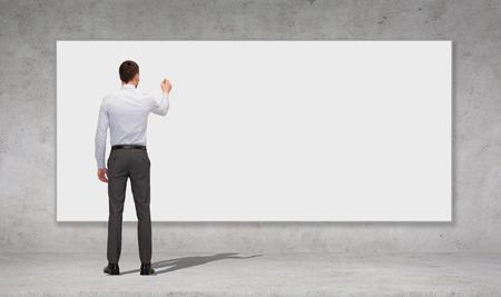 ビジネス、教育、オフィスの人々 コンセプト - ビジネスマンや背面からコンクリートの壁の背景の上空白のホワイト ボードに何かを図面を書いたり